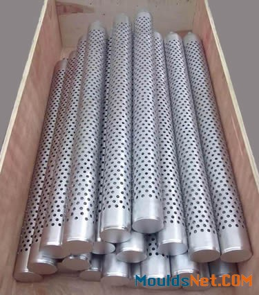 A lot of stainless steel perforated candle filters in a wooden box.