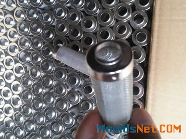 Many stainless steel woven cylindrical filter elements in a carton.